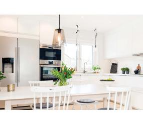 Modern white kitchen space with stainless steel appliances and accessories
